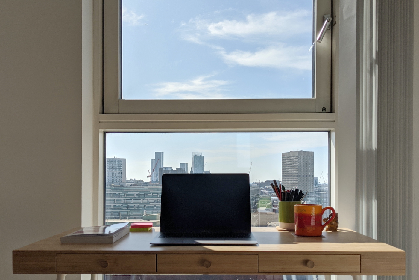 Laptop open on a desk in front of a window, out that window a blue sky and Manchester skyline